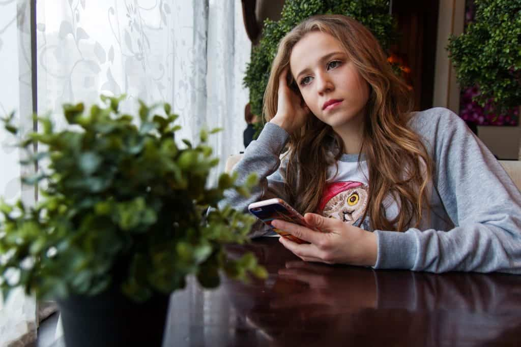 A young lady holding a phone leaning on her hand looking sad