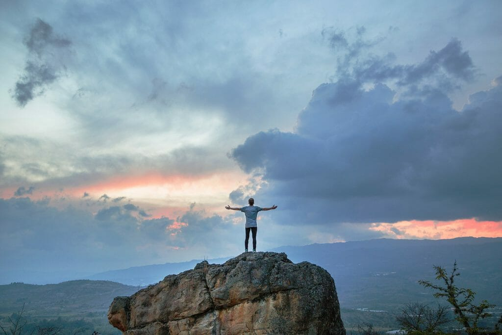 How to get success in life person on rock in front of clouds