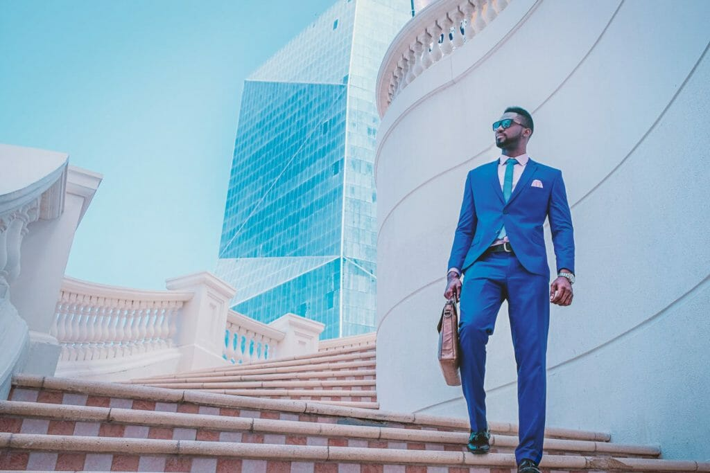 Signs of success man in blue suit walking down steps outside