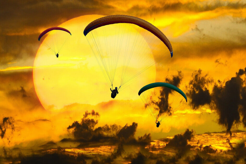 Seizing opportunity. Paragliders over a sunset